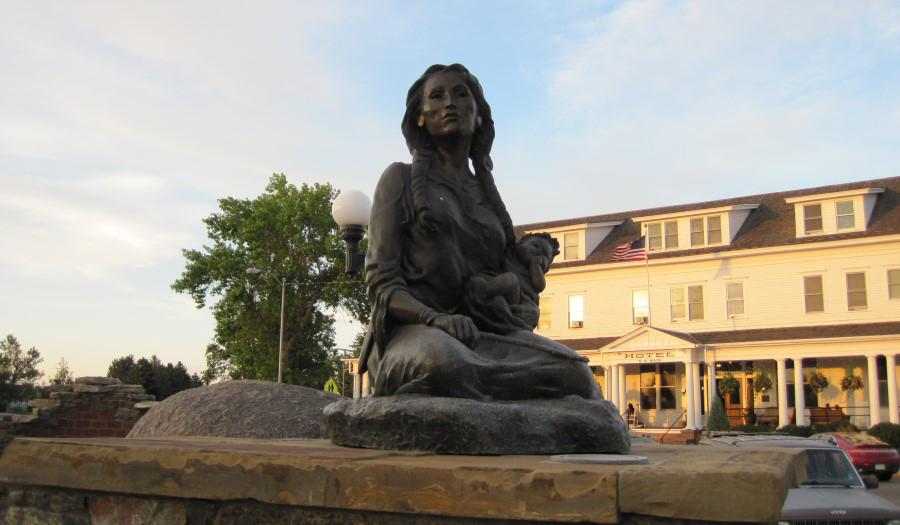 "Statue of Sacajawea in Sacajawea Park near the Headwaters Trail System in Three Forks, Montana | Photo by Emmett Cartier, <a href=""https://www.flickr.com/photos/greaterglory/19812112426/sizes/l"">Greater Glory Flickr Page</a>"