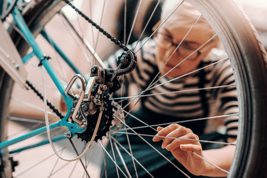 Woman repairs a bicycle | Photo courtesy iStock by Getty Images