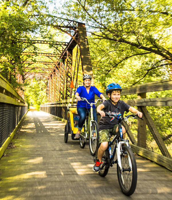 Adria Hamel with son Jacob and daughter Hailey enjoy a bike ride over the Sangamon River Trail bridge, which runs along the Heartland Pathways. | Photo by Chris Bucher