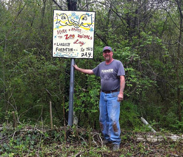 Joel Slaton, creator of the Dolls Head Trail, with a sign by artist Kyle Brooks (BlackCatTips.com) | Photo by Kyle Brooks